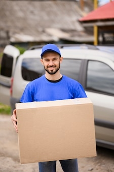 Portrait of handsome delivery man carrying parcel