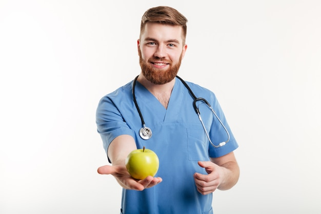 Portrait of handsome doctor in blue coat looking at camera