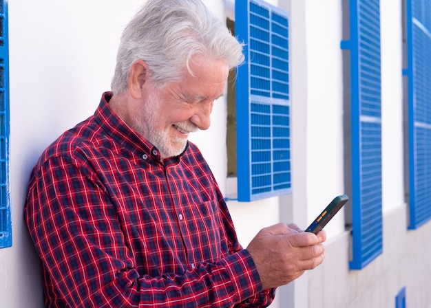 Portrait of a handsome elderly man standing outdoor on a white background using mobile phone. joyful elderly with white hair and checkered shirt