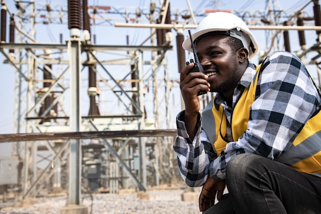 Portrait of handsome engineering man using walkie talkie and wear hardhat in front of high power power plant. back view of contractor on background of modern buildings.