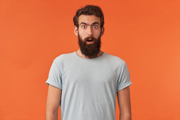 Portrait of handsome european or bearded young man with brown eyes in white t-shirt is looking at you emotion surprised confused and attentive posing standing