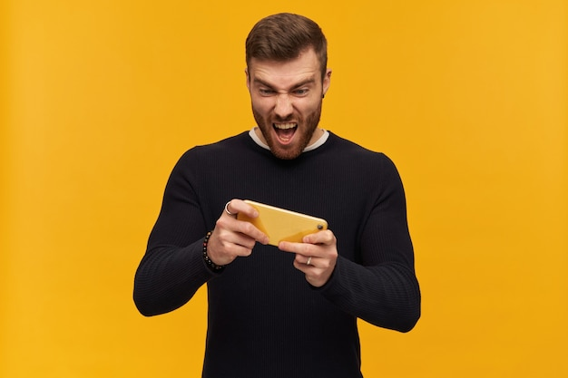 Portrait of handsome, excitable male with brunette hair and beard. has piercing. wearing black sweater. playing videogame on his smartphone. stand isolated over yellow wall