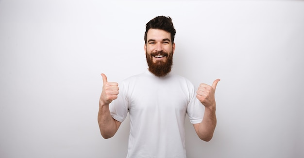 Portrait of handsome and excited bearded man showing thumbs up over white wall