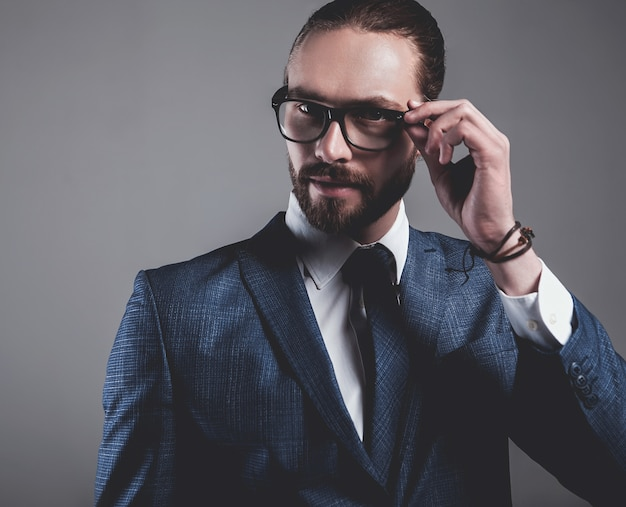 Portrait of handsome fashion businessman model dressed in elegant blue suit with glasses