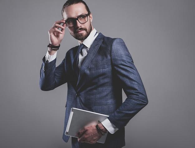 Portrait of handsome fashion businessman model dressed in elegant blue suit with glasses