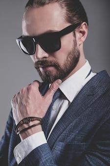 Portrait of handsome fashion businessman  model dressed in elegant blue suit with sunglasses