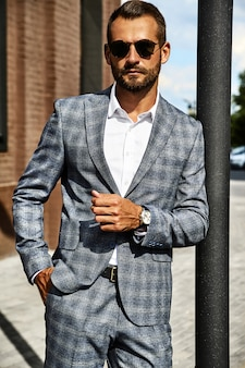 Portrait of handsome fashion businessman model dressed in elegant checkered suit posing on street