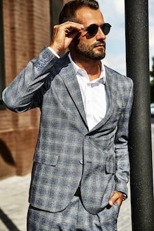 Il ritratto del modello bello dell'uomo d'affari di modo si è vestito in vestito a quadretti elegante che posa sulla via