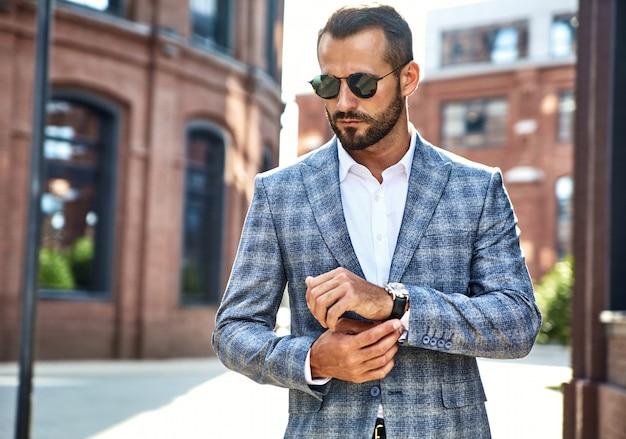 Portrait of handsome fashion businessman model dressed in elegant checkered suit posing on street