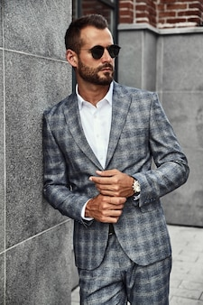 Portrait of handsome fashion businessman model dressed in elegant checkered suit