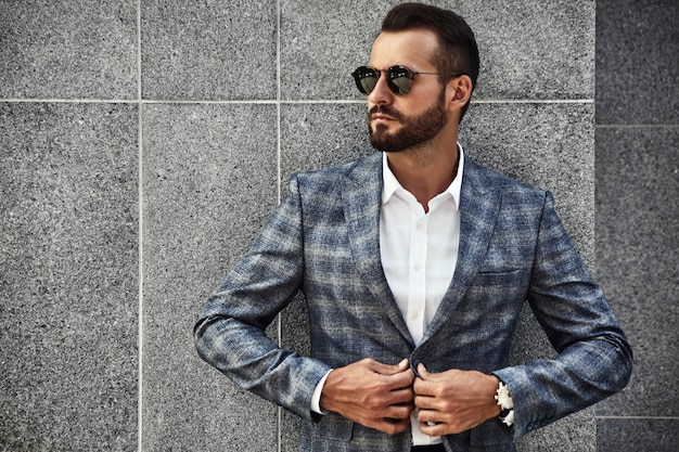Portrait of handsome fashion businessman model dressed in elegant checkered suit