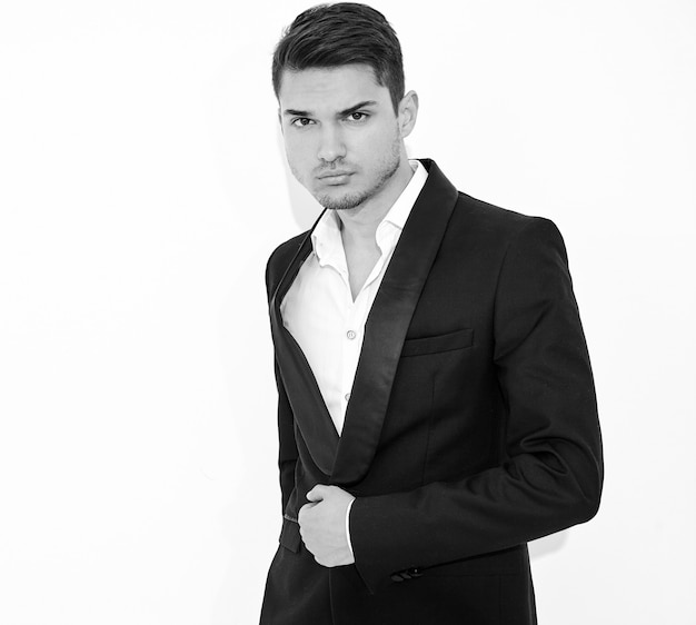 Portrait of handsome fashion stylish businessman model dressed in elegant black classic suit posing. metrosexual