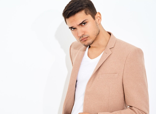 Portrait of handsome fashion stylish businessman model dressed in elegant light pink suit posing. metrosexual