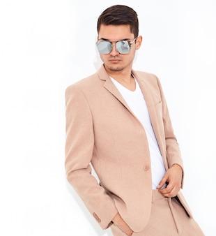 Portrait of handsome fashion stylish businessman model dressed in elegant light pink suit posing. metrosexual