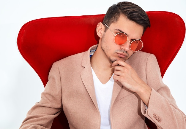 Portrait of handsome fashion stylish businessman model dressed in elegant light pink suit sitting on red chair. metrosexual