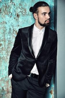 Portrait of handsome fashion stylish hipster businessman model dressed in elegant black suit