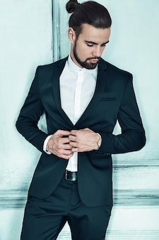 Portrait of handsome fashion stylish hipster businessman model dressed in elegant black suit