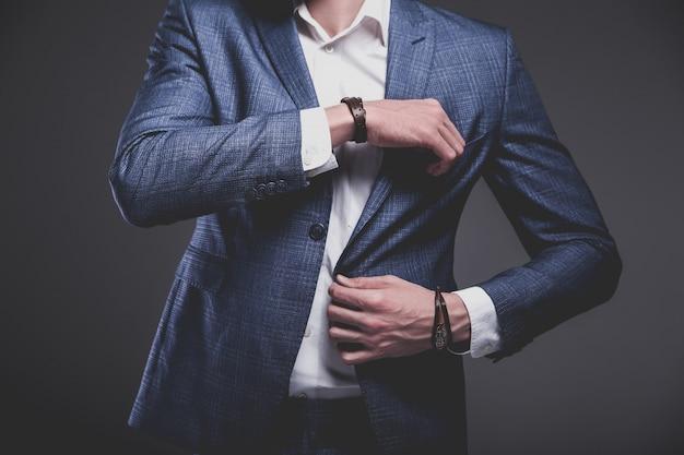 Portrait of handsome fashion stylish hipster businessman model dressed in elegant blue suit on gray