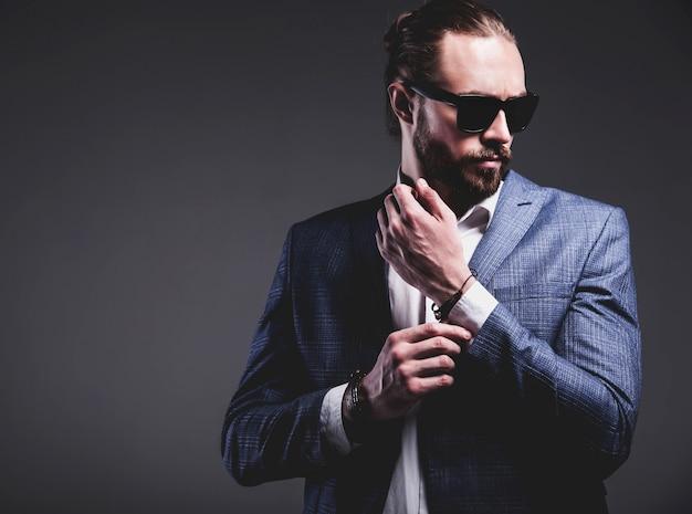 Il ritratto del modello dell'uomo d'affari alla moda dei pantaloni a vita bassa alla moda bello si è vestito in vestito blu elegante che posa sul gray.