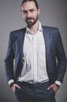 Portrait of handsome fashion stylish hipster businessman model dressed in elegant blue suit posing on gray