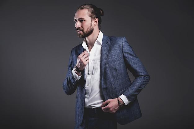 Portrait of handsome fashion stylish hipster businessman model dressed in elegant blue suit posing on gray