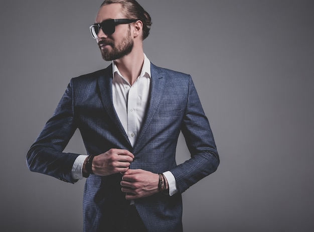 Portrait of handsome fashion stylish hipster businessman model dressed in elegant blue suit in sunglasses posing on gray