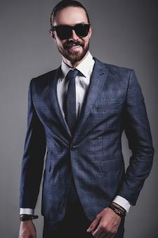 Portrait of handsome fashion stylish hipster businessman model dressed in elegant blue suit