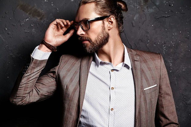 Portrait of handsome fashion stylish hipster businessman model dressed in elegant brown suit in glasses near dark wall