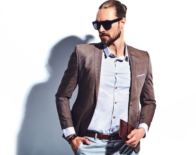Portrait of handsome fashion stylish hipster businessman model dressed in elegant brown suit in sunglasses