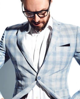 Portrait of handsome fashion stylish hipster businessman model dressed in elegant light blue suit in glasses on white
