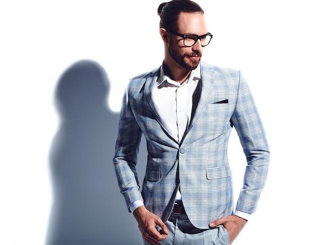 Portrait of handsome fashion stylish hipster businessman model dressed in elegant light blue suit in glasses on white