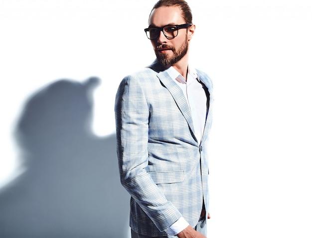 Portrait of handsome fashion stylish hipster businessman model dressed in elegant light blue suit in glasses on white.