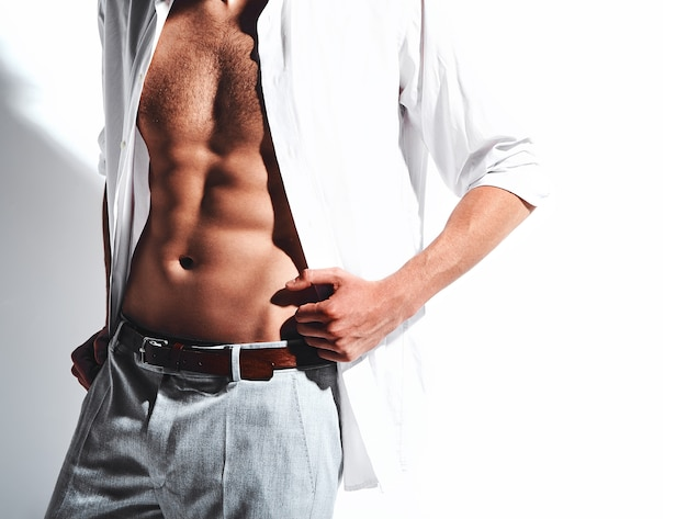 Portrait of handsome fashion stylish hipster model man in classic shirt with bare chest on white