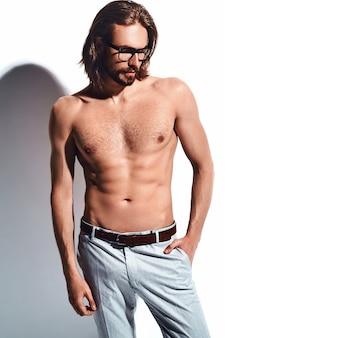 Ritratto di uomo di modello di hipster alla moda alla moda bello con petto nudo in bicchieri su bianco