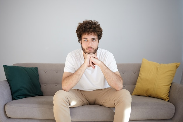 Portrait of handsome fashionable young bearded guy in his twenties having rest indoors with calm facial expression, placing chin on clasped hands, sitting on comfortable couch