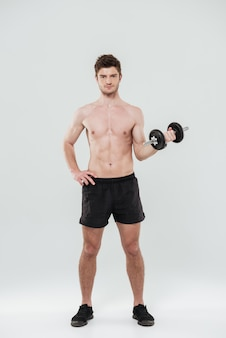 Portrait of a handsome fit sportsman standing and holding dumbbell