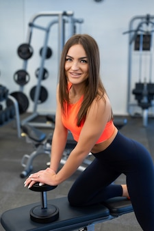 Portrait handsome fit woman lifting dumbbells on bench at gym