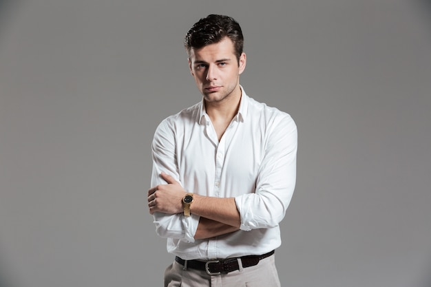 Ritratto di un uomo concentrato bello nella posa bianca della camicia