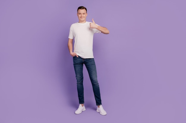 Portrait of handsome funny man show thumb up on purple background