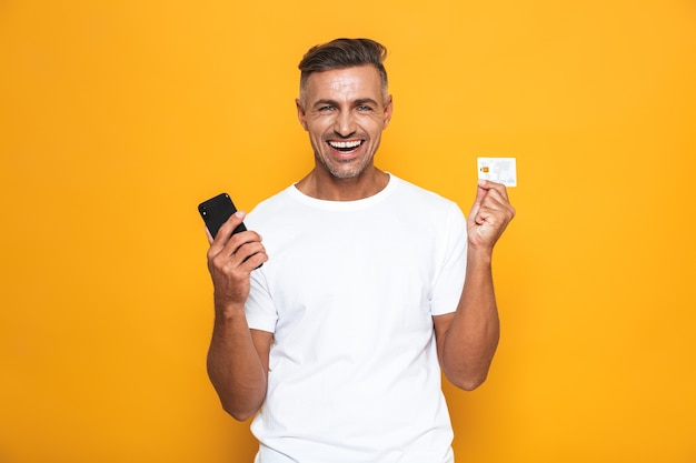 Portrait of handsome guy 30s in white t-shirt holding mobile phone and credit card isolated on yellow