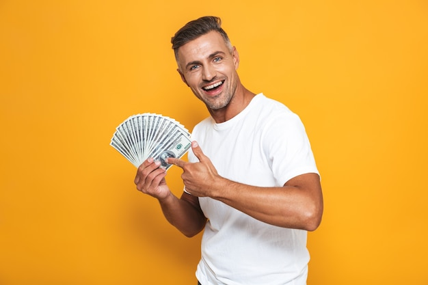 Portrait of handsome guy 30s in white t-shirt smiling and holding bunch of money isolated on yellow
