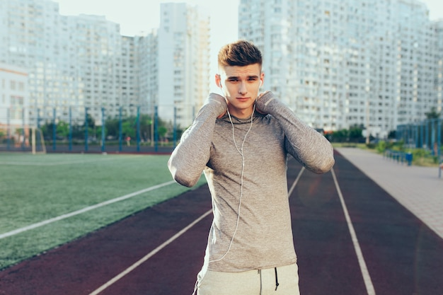 Portrait of handsome guy in gray sport suit on running track on city background in the morning. he wears gray sport suit, headphones. he is looking to camera.