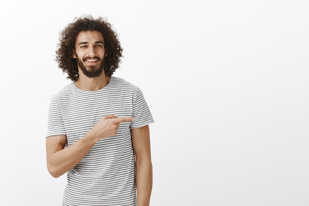 Portrait of handsome guy with charming smile and curly hair in casual clothes, pointing right and smiling with assured expression