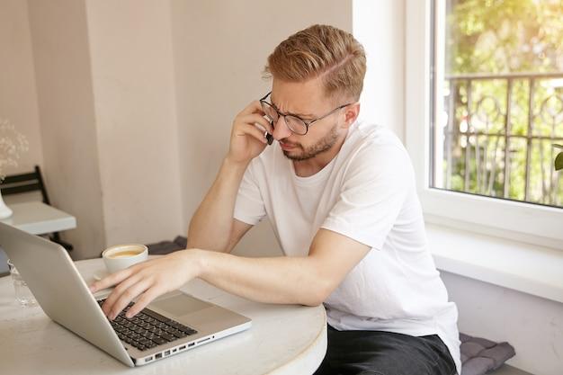 Ritratto di bel ragazzo con taglio di capelli corto che risolve problemi al telefono, lavora in remoto in un luogo pubblico, aggrottando le sopracciglia e guardando perplesso