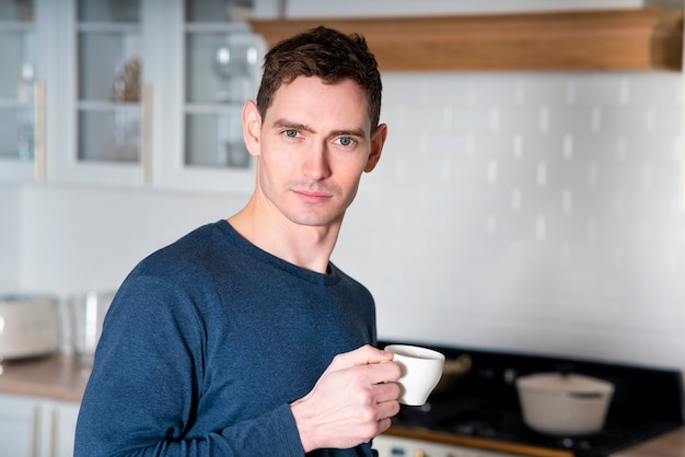 Portrait of handsome guy, young european man drinking coffee or tea from mug in early morning at