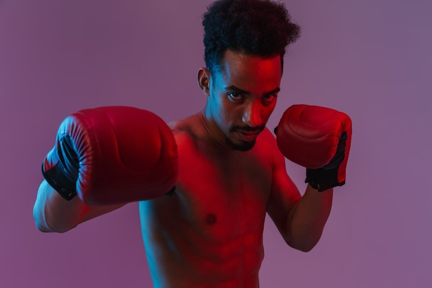 Portrait of handsome half-naked african american man posingin boxing gloves isolated over violet wall