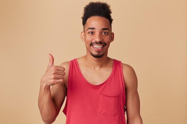 Ritratto di bello, felice maschio afroamericano con barba e acconciatura afro. indossare canottiera rossa. mostra il segno del pollice in su, tutto bene sul muro beige pastello