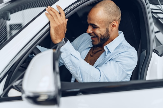 Portrait of a handsome happy african american man sitting in his newly bought car close up