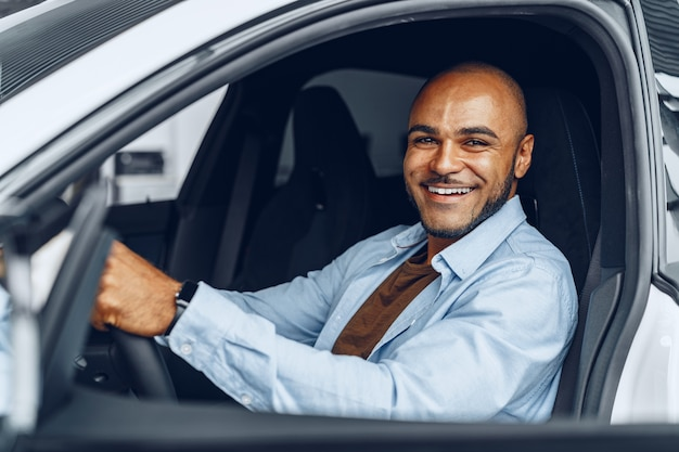 Portrait of a handsome happy african american man sitting in his newly bought car