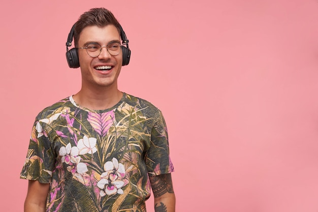 Portrait of handsome happy male with short hair standing, wearing headphones and taking pleasure in music, looking aside with charming smile
